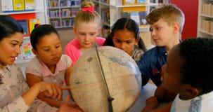 Asiatischer weiblicher Lehrer, der bei Tisch die Kinder ?ber die Kugel in der Schulbibliothek 4k unterrichtet stock footage
