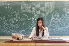 Asiatischer weiblicher Lehrer, der in einer Klassenzimmermarkierungshausarbeit der Studenten sitzt stockbild