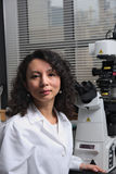 Asiatischer weiblicher Wissenschaftler, der am Mikroskop sitzt Stockbilder