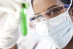 Asiatischer weiblicher Wissenschaftler u. Reagenzglas der grünen Flüssigkeit Stockbild