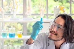 Asiatischer Wissenschaftler, der flüssige Substanz im Reagenzglas überprüft stockbilder