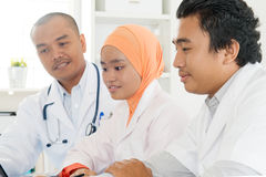 Asiatisches Ärzteteam, das im Krankenhausbüro sich bespricht Stockfotos