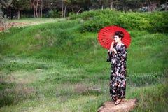 Asiatisches Artportrait der Frau mit Regenschirm Stockfoto