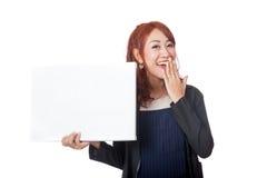 Asiatisches Büromädchen, das mit einem leeren Zeichen lacht Lizenzfreies Stockbild