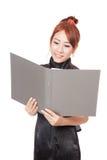 Asiatisches Büromädchen ist glückliche Lesedaten in einem Ordner und in einem Lächeln Lizenzfreies Stockfoto