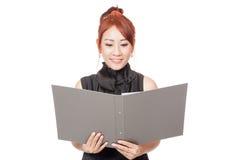 Asiatisches Büromädchen ist glückliche Lesedaten in einem Ordner und in einem Lächeln Stockfotos