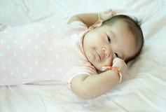 Asiatisches Baby, das auf Bett legt Lizenzfreie Stockfotos