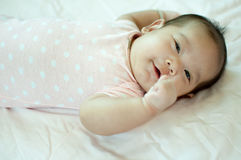 Asiatisches Baby, das auf Bett legt Lizenzfreie Stockfotografie