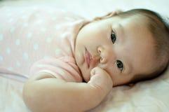Asiatisches Baby, das auf Bett legt Stockfoto