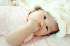 Asiatisches Baby, das auf Bett legt Stockbild