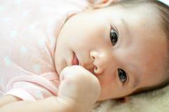 Asiatisches Baby, das auf Bett legt Stockfotografie