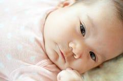Asiatisches Baby, das auf Bett legt Lizenzfreies Stockfoto