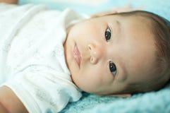 Asiatisches Baby, das auf Bett legt Stockfotos