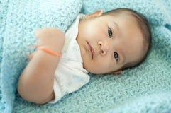 Asiatisches Baby, das auf Bett legt Stockbilder