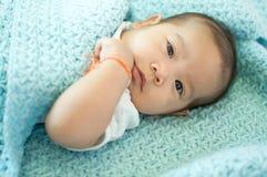 Asiatisches Baby, das auf Bett legt Lizenzfreie Stockbilder