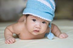 Asiatisches Baby, das auf blauer Kleidung liegt Lizenzfreie Stockfotografie