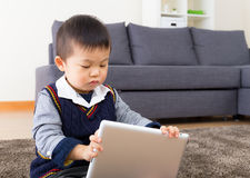 Asiatisches Baby, das digitale Tablette verwendet Stockfotos
