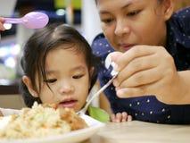 Asiatisches Baby, das einen schaufelnden Reis des Löffels durch ihre Mutter betrachtet, um sie einzuziehen Stockfotografie