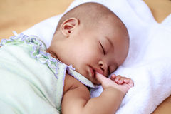 Asiatisches Baby, das ihren Daumen saugt Stockbilder