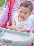 Asiatisches Baby, das im Spaziergänger lächelt Stockbild