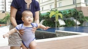 Asiatisches Baby, das lernt zu stehen stock video