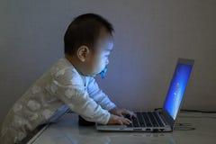 asiatisches Baby, das mit Laptop arbeitet stockfoto
