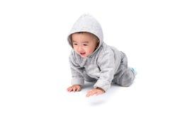 Asiatisches Baby in der grauen Jacke mit einer Haube, lokalisiert auf weißem backgro Stockfoto