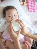 Asiatisches Baby essen Milch von der Flasche Lizenzfreies Stockbild