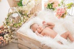 Asiatisches Baby innerhalb eines Kastens mit weißer Decke, Blumen aroud Lizenzfreie Stockfotografie