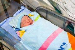 Asiatisches Baby mit nettem Gesicht Schlafbrunnen und bedecken das blaue bla stockbild