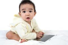 Asiatisches Babyspielspiel mit Tablet-PC Stockfotografie
