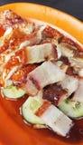 Asiatisches Brathähnchen und Schweinebauch auf orange Platte Lizenzfreie Stockbilder