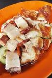Asiatisches Brathähnchen und Schweinebauch auf orange Platte Stockfoto