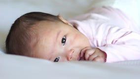 Asiatisches chinesisches Babyrollen auf Bett und Schauen neugierig stock video footage