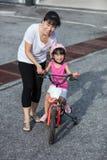 Asiatisches chinesisches Fahrrad des kleinen Mädchens Reitmit Mutterführer Lizenzfreies Stockbild