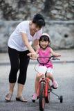 Asiatisches chinesisches Fahrrad des kleinen Mädchens Reitmit Mutterführer Stockbilder