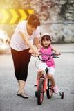 Asiatisches chinesisches Fahrrad des kleinen Mädchens Reitmit Mutterführer Lizenzfreie Stockfotos