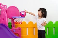 Asiatisches chinesisches kleines Mädchen, das Basketball spielt Lizenzfreie Stockbilder