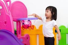 Asiatisches chinesisches kleines Mädchen, das Basketball spielt Stockfoto