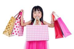Asiatisches chinesisches kleines Mädchen, das Einkaufstaschen hält lizenzfreie stockfotos