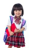 Asiatisches chinesisches kleines Studentenmädchen mit Schultasche und Büchern Lizenzfreie Stockfotos