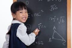 Asiatisches chinesisches Schreiben des kleinen Mädchens auf Tafel stockfoto