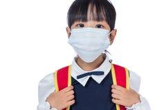 Asiatisches chinesisches Schulmädchen mit Schultasche und tragender Maske Lizenzfreie Stockfotos