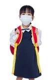 Asiatisches chinesisches Schulmädchen mit Schultasche und tragender Maske Stockfotos