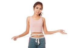 Asiatisches dünnes Mädchen, das ihre Taille mit Band misst Stockfoto