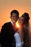 Asiatisches Eleganzhochzeits-Paare ourdoor mit Sonnenuntergang backgound Stockfotos