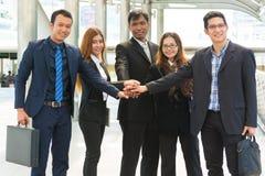 Asiatisches Geschäfts-Team, das zusammen Einheit mit ihren Händen zeigt stockbild