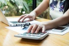 Asiatisches Geschäfts-womanAsian Geschäftsfrau, die einen Taschenrechner zu c verwendet Stockfotos