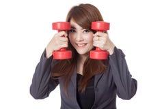Asiatisches Geschäftsfraulächeln setzte ihr Gesicht zwischen drumbbells Lizenzfreies Stockfoto