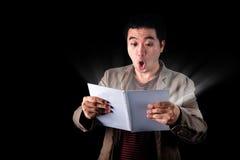 Asiatisches Geschäftsmannoffenes buch mit dem Licht, das von den Seiten auf Dunkelheit kommt Lizenzfreies Stockbild